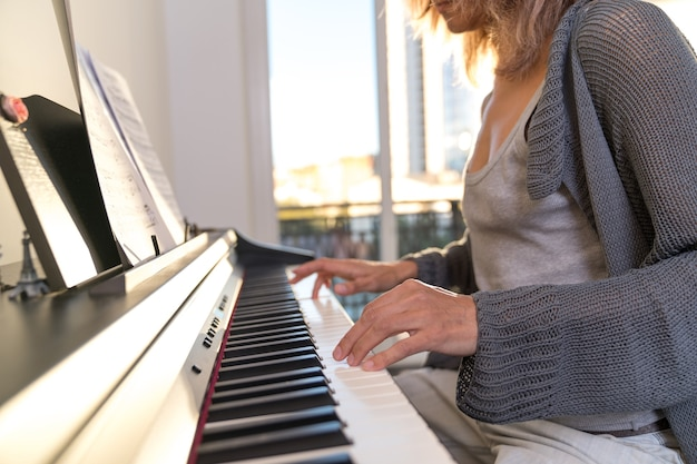 Hands of a woman playing the electronic piano against the background of a large window