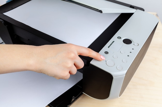 Hands of a woman using a copying machine close up