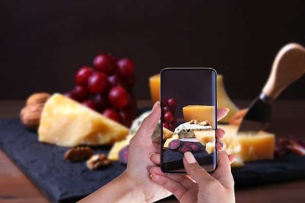 Hands of woman with smartphone taking photo assorted cheeses. dark and moody style.