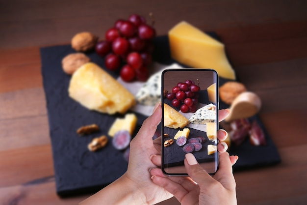 Hands of woman with smartphone taking photo assorted cheeses, nuts, grapes, fruits, smoked meat and a glass of wine.