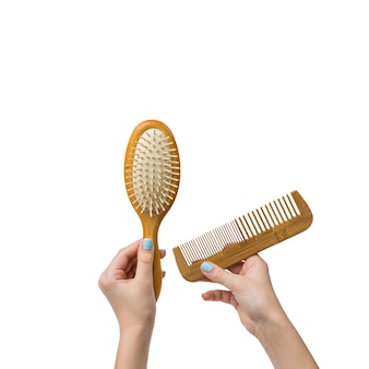 Hands of a woman with two wooden combs isolated on a white background. tools for hair care.