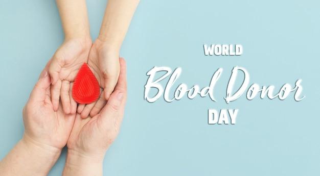 Руки женщины держат каплю крови концепция сдачи крови переливания крови