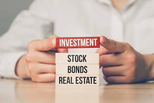 Hands over wooden blocks with inscriptions of bonds, investment, real estate and stock