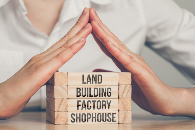 Hands over wooden blocks with the inscriptions land, building, factory and shophouse