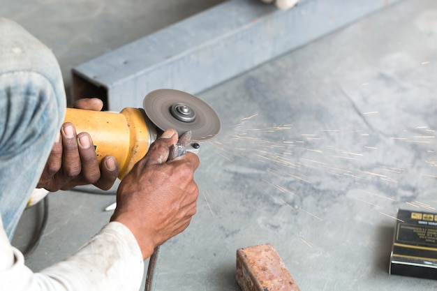 Hands of worker using angle grinder tool to cutting steel bar with fire sparking.