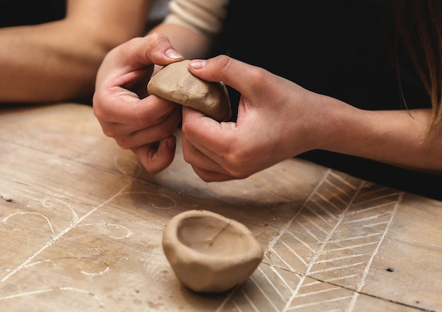 Hands working and finishing sculpture with clay on wooden table in workshop