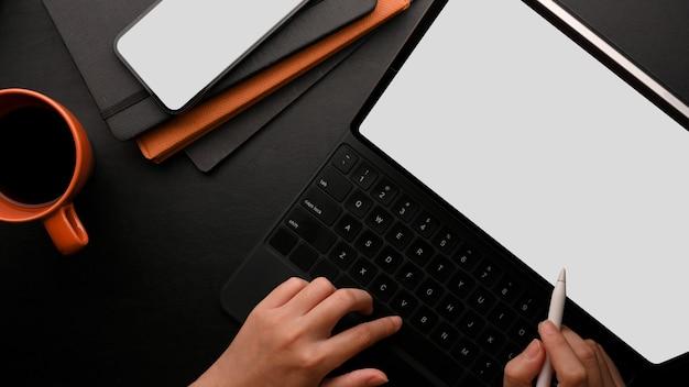 Руки, работающие на черном планшете с клавиатурой, макет мобильного телефона, кофейные ноутбуки на черном столе