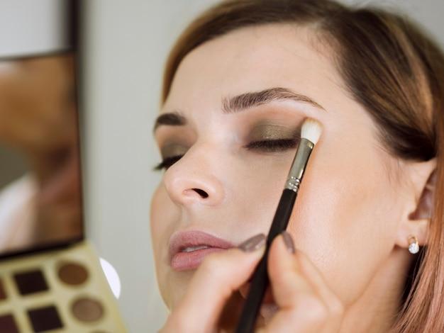 Руки работают над макияжем клиента