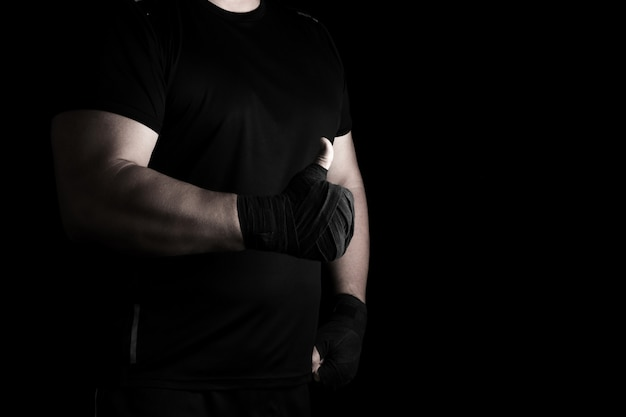 Hands wrapped in black elastic sports bandage show a like sign