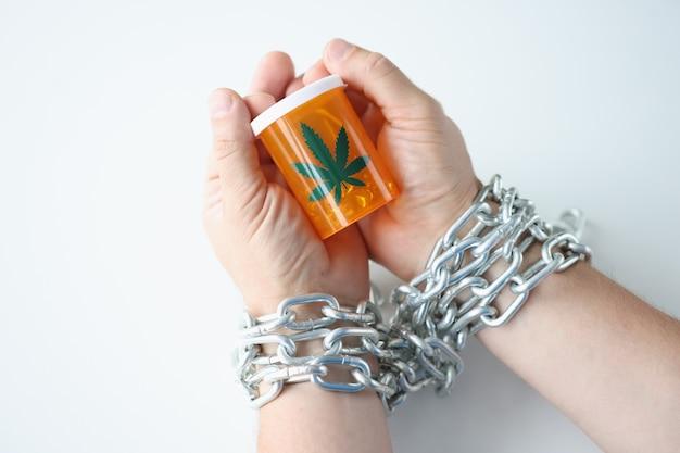 사슬에 싸인 손은 마리화나 중독과 약물 치료 개념의 항아리를 들고 있습니다.