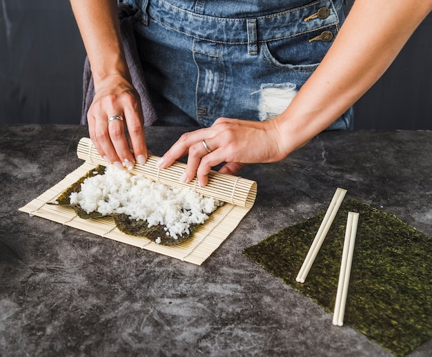 Hands wrapping with sushi mat
