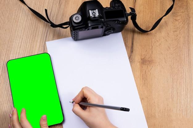 空白の白いページ、カメラ、スマートフォンで書く手