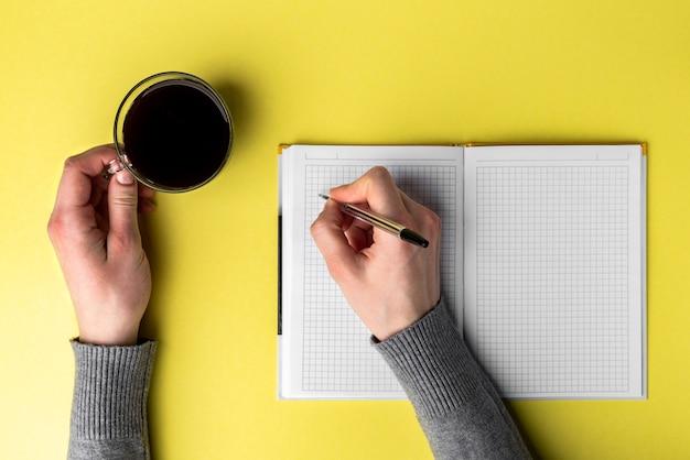 開いたノートに書き込み、黄色の背景にコーヒーのカップを保持している手。