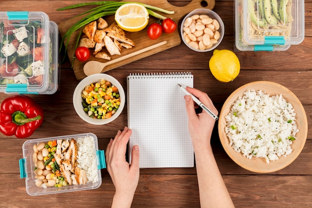 Hands writing on notebook with casseroles ad food