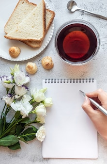 Hands writing on a notepad breakfast setting copy space