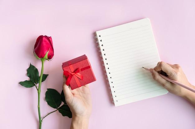 バラとピンクのギフトボックスでノートに書く手