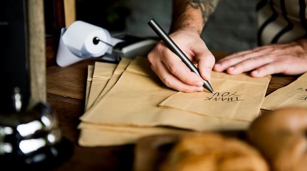 Руки, пишущие спасибо на бумажном мешке