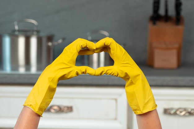 Hands in yellow gloves in the kitchen