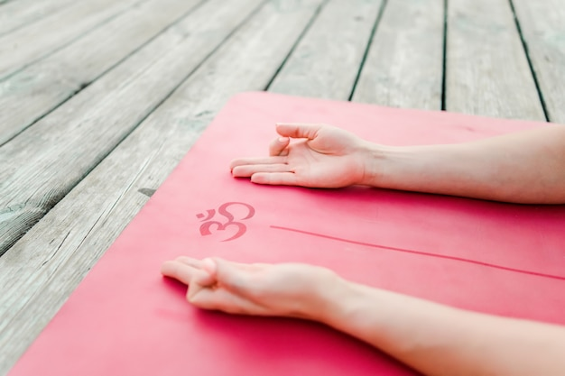 Hands on a yoga mat with an om mantra symbol