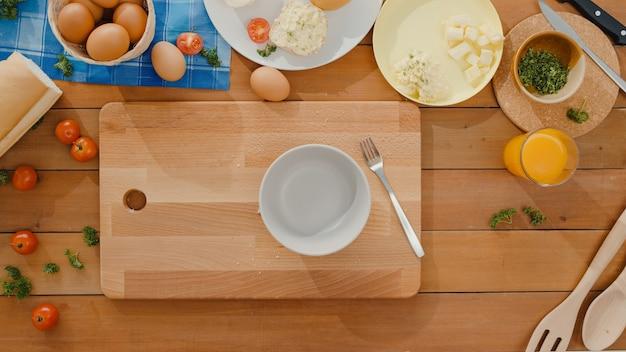 Mani di giovane donna asiatica chef cracking uovo nella ciotola di ceramica e cucinare frittata