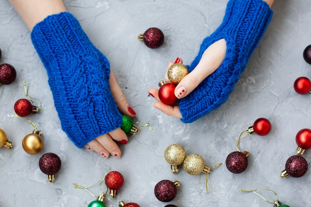 Hands of young beautiful woman in blue mittens holding christmas balls