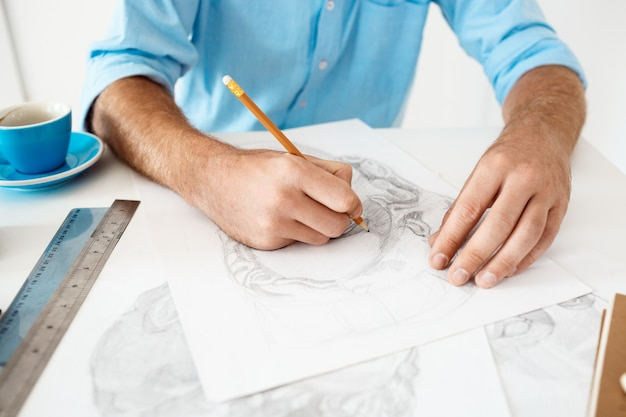 Hands of young businessman sitting at table with pencil drawing portrait. white modern office interior.