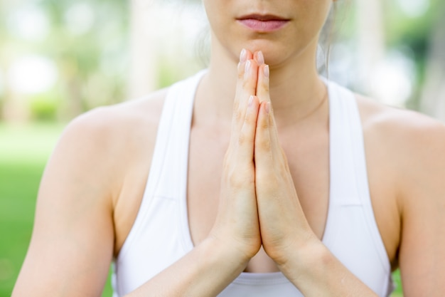 Hands of young caucasian woman praying outdoors