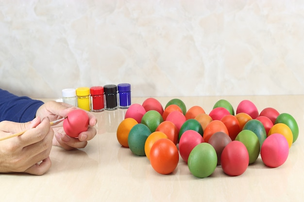 Hands of young christian coloring eggs on marble top background preparing for easter day.