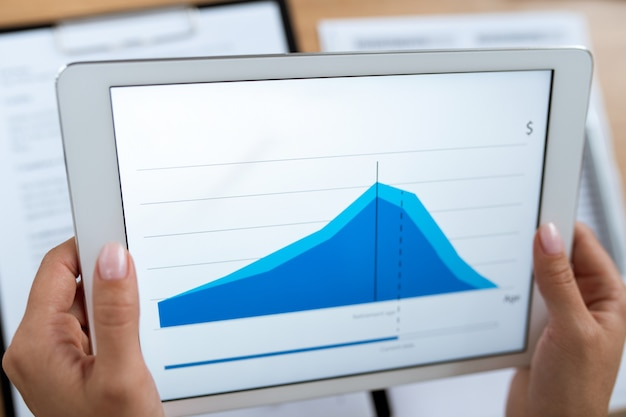 Hands of young contemporary real estate agent or financial advisor holding tablet with rate change graph