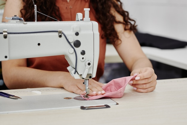Hands of young contemporary seamstress sewing shoulder pads of pink color while sitting by machine and finishing work over new item