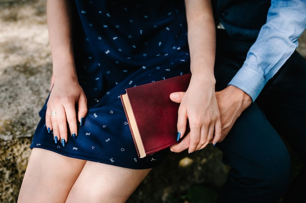 A hands young couple holds closed book on the knees