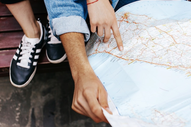 Hands of young couple on touristic map