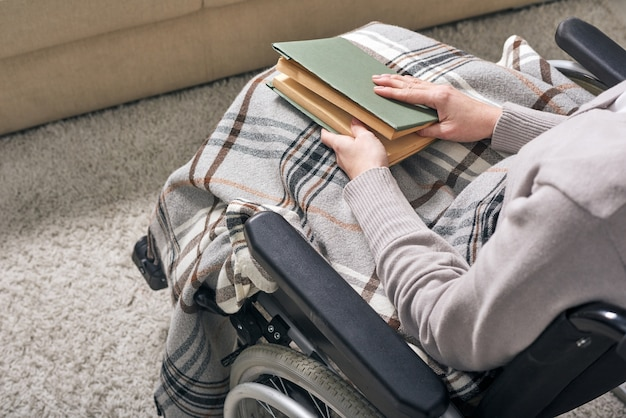 Hands of young disable woman holding book on her knees while sitting in wheelchair and spending time at home