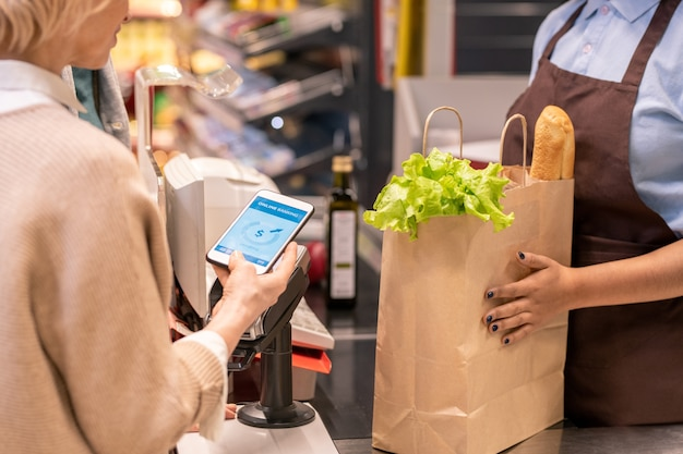 Hands of young female cashier or shop assistant holding paper sack with bread and lettuce leaves while customer paying for the goods