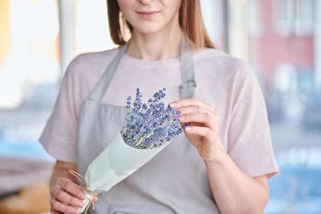 Hands of young female florist packing bunch of lavender into paper while working in studio