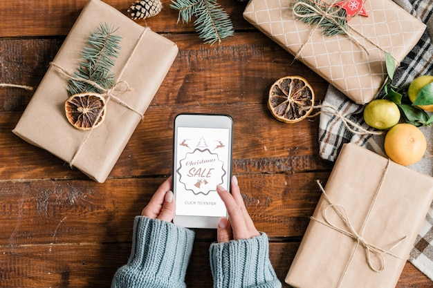 Hands of young female shopper going to enter online shop to order gifts for christmas over packed presents on wooden table