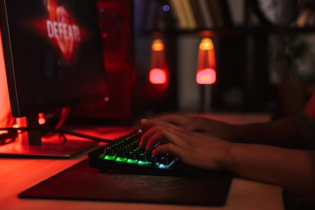 Hands of young gamer man playing video games on computer in dark room, using backlit colorful keyboard