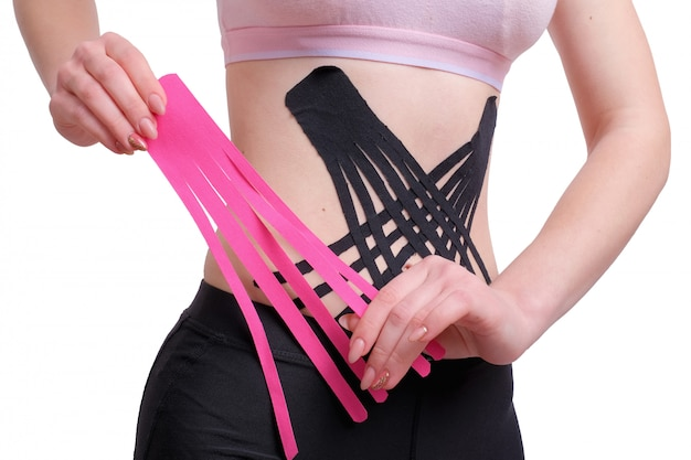 Hands of young girl applying pink kinesio tape on the her abdomen