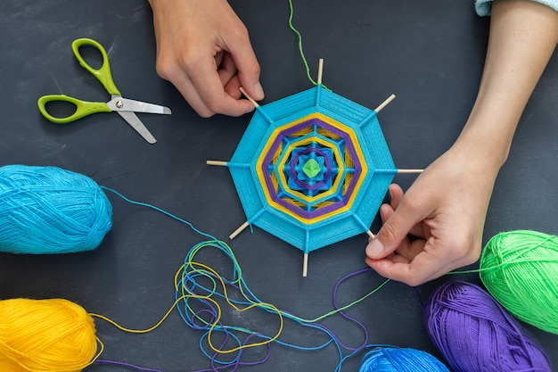 Hands of young girl keep handmade mandala
