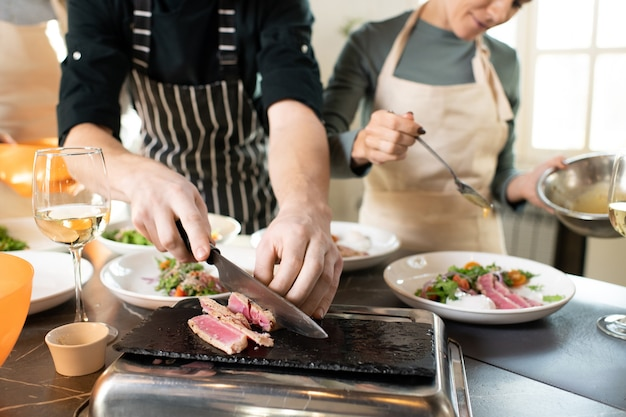 Hands of young male cooking coach chopping piece of smoked beef on special board by table among plates with served vegetable salad