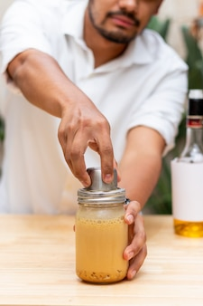 The hands of a young man closing a cocktail shaker filled with liquor and milk on ice