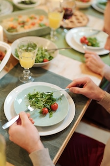 Hands of young man holding knife and spoon over plate with fresh green salad and tomates during family dinner