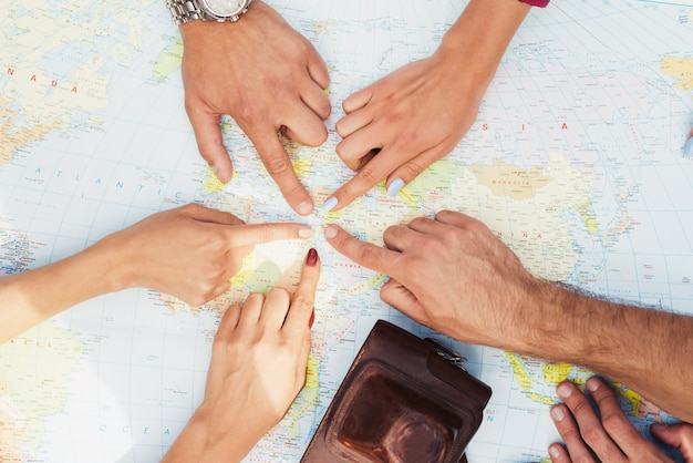 Hands of young people are pointing to travel map.