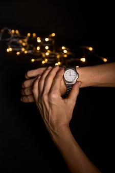 Hands of a young person looking at a clock about to mark the first second of the new year 2019