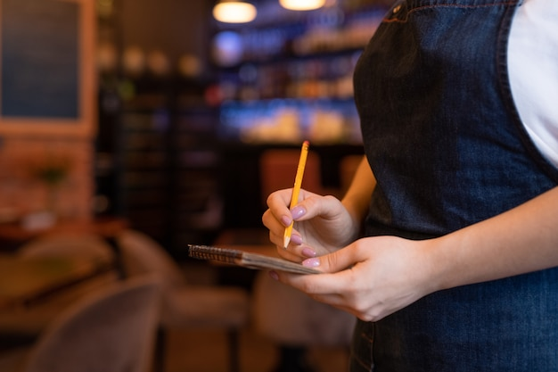 Hands of young waitress in dark blue apron holding pencil over page of notepad while going to write down order of client in restaurant