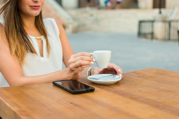 Hands of a young woman are holding a cup of coffee on a terrace of a pub