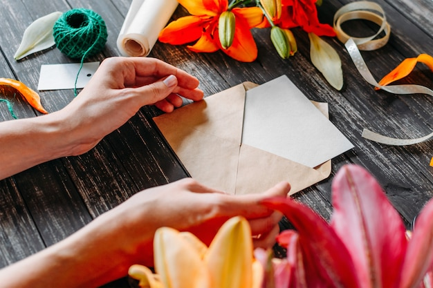 Hands of young woman florist or designer creating greeting card on wooden table with colored flowers