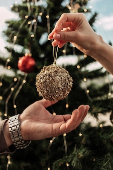 Hands of young woman giving golden decorating christmas toy ball to her man to put them on christmas tree before celebration
