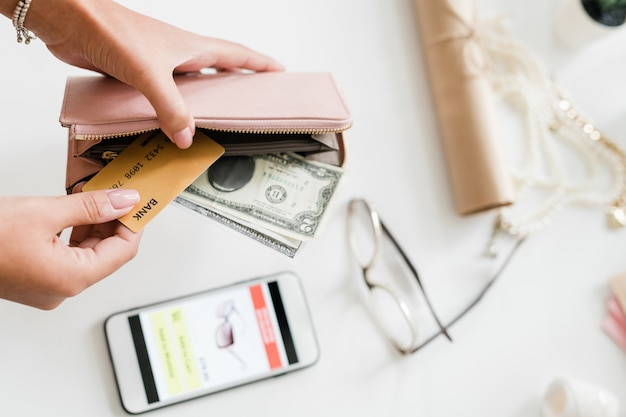 Hands of young woman holding nude beige leather wallet with dollar bills and plastic card over smartphone and eyeglasses on desk