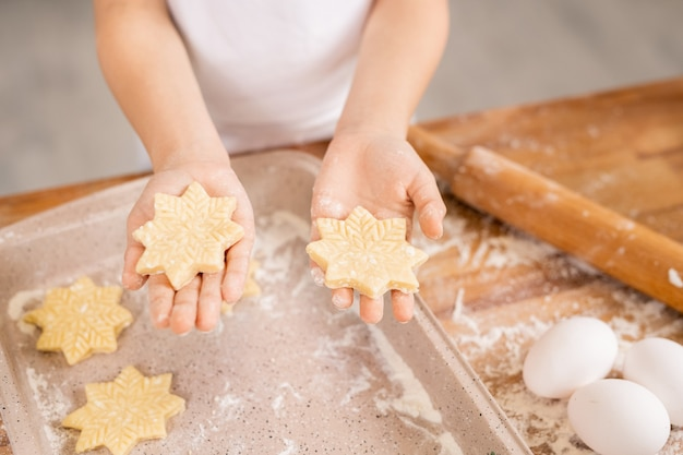 Hands of young woman holding raw snowflake shaped cookies over tray on kitchen table covered with flour
